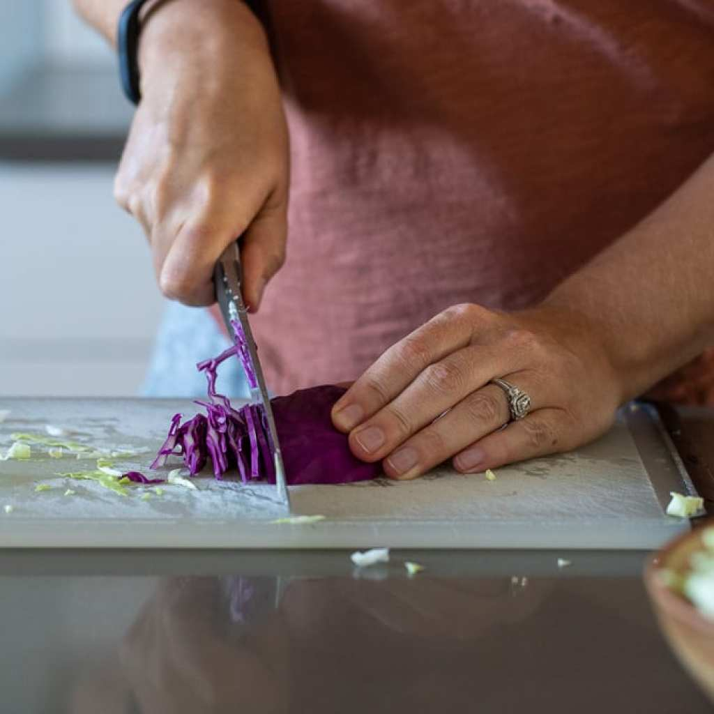 woman slicing purple cabbage for salad on plastic cutting board