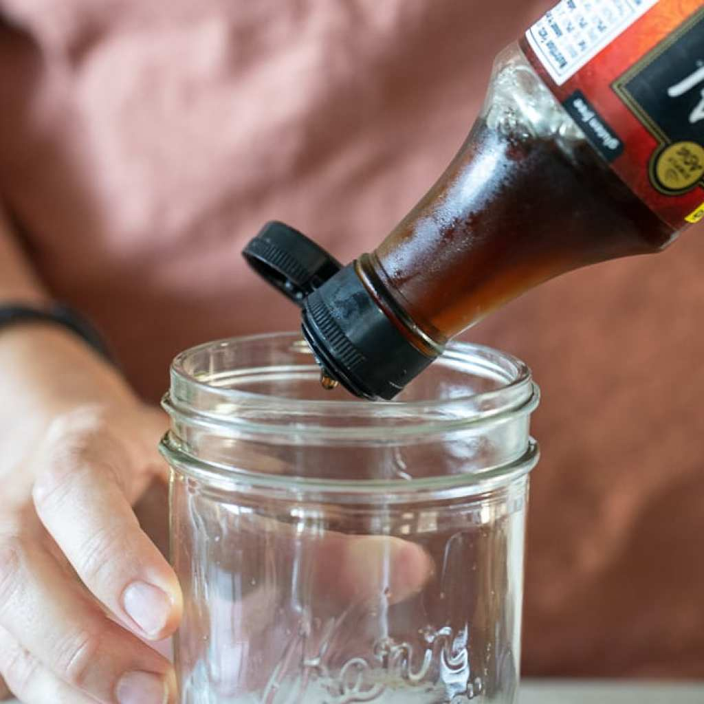 woman pouring fish sauce into mason jar for dressing