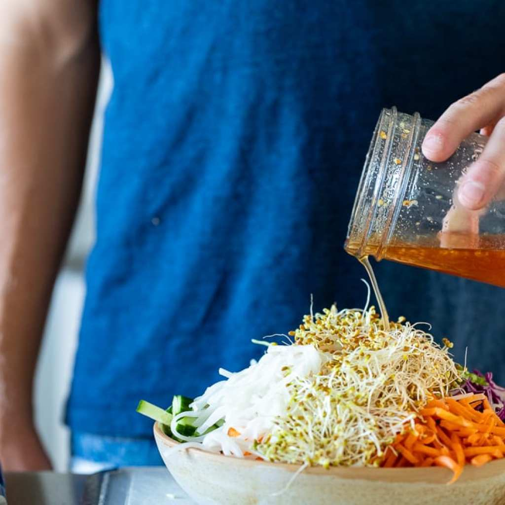 boy pouring dressing over Vietnamese salad from mason jar