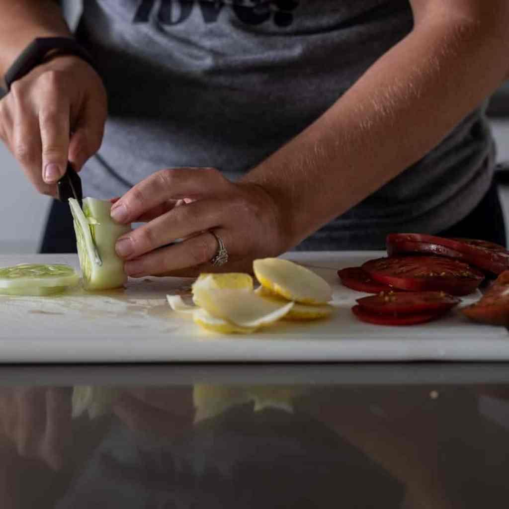 woman slicing a lemon cucumber on a white plastic cutting board