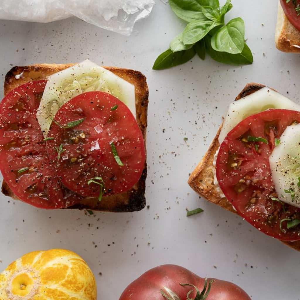 open -faced cucumber and tomato toast on a marble surface