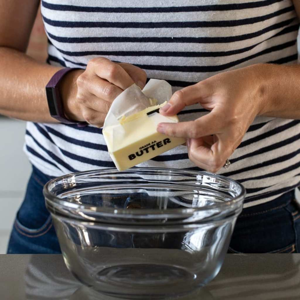 woman adding butter to a glass bowl