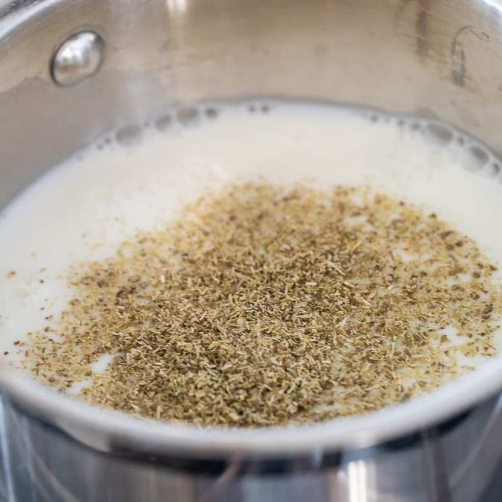 steeping tea in a small stainless steel pan in milk and chamomile