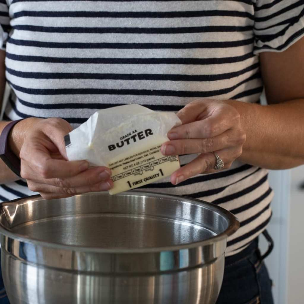 woman adding softened butter to stainless steel bowl for a lemon chamomile bundt cake