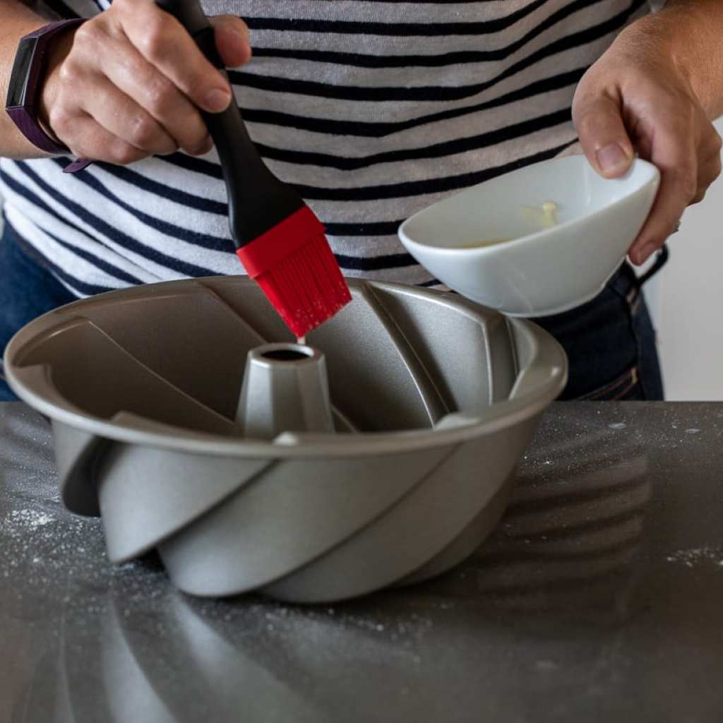 woman brushing bundt cake with melted butter