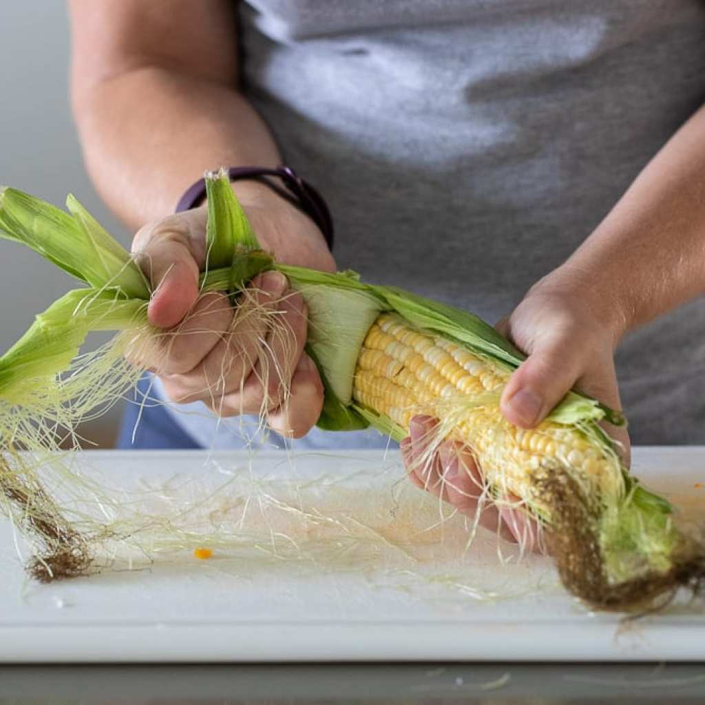 woman shucking corn on white plastic cutting board