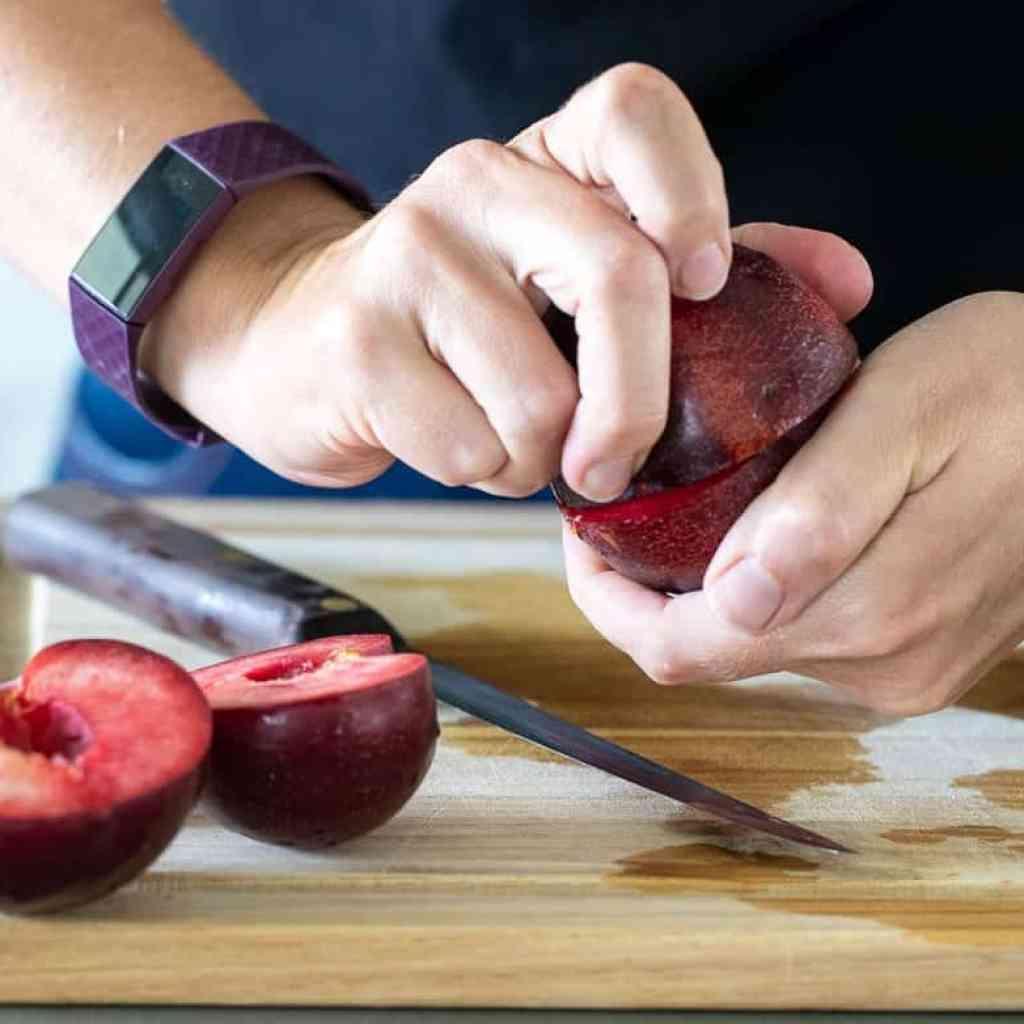 woman twisting plum in half