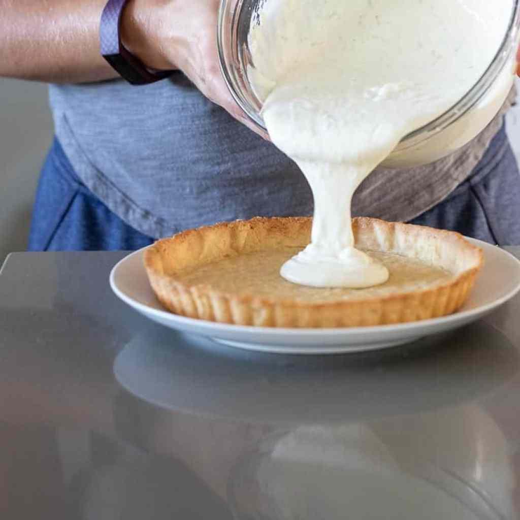 woman adding no-bake cheesecake filling to tart pan.