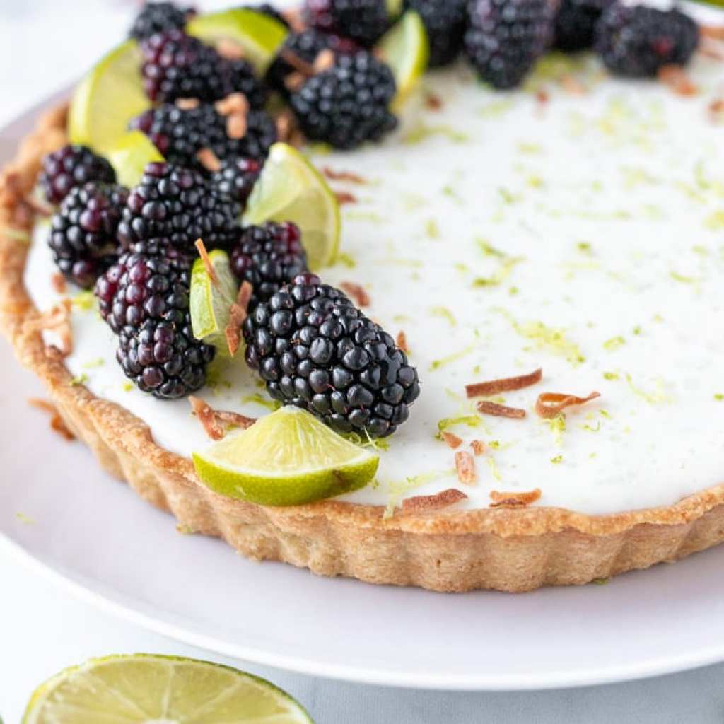 Easy No-Bake Lime Cheesecake with blackberries and toasted coconut tart on white dinner plate