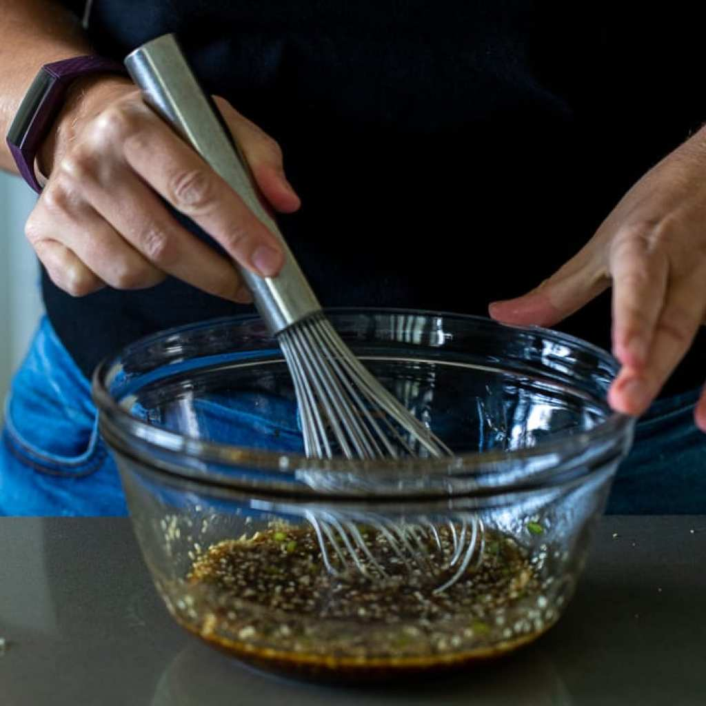 woman mixing marinating mix for beef bulgogi in clear glass bowl