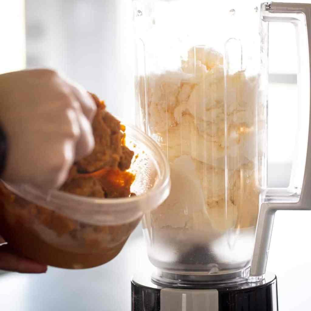 woman adding pumpkin puree to ice cream in blender