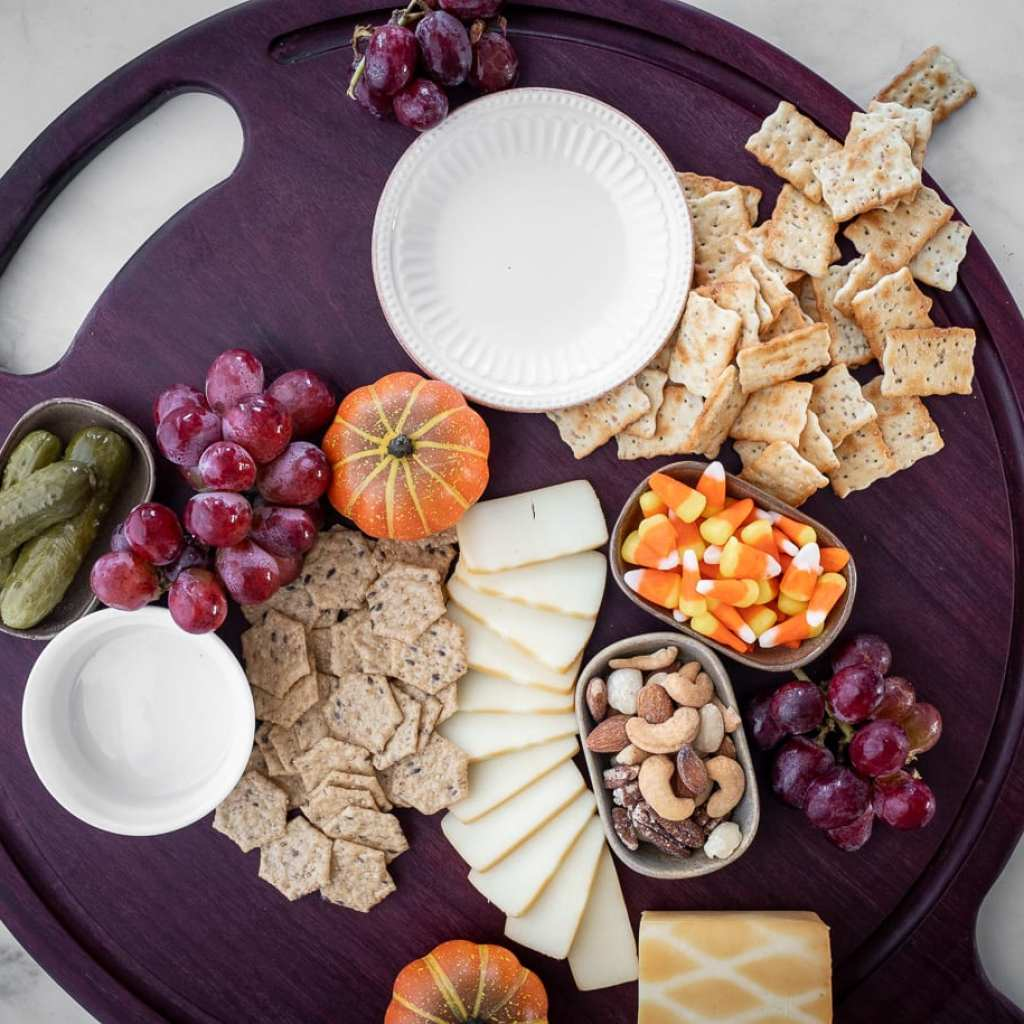 adding crackers and fruit and candy to a charcuterie board