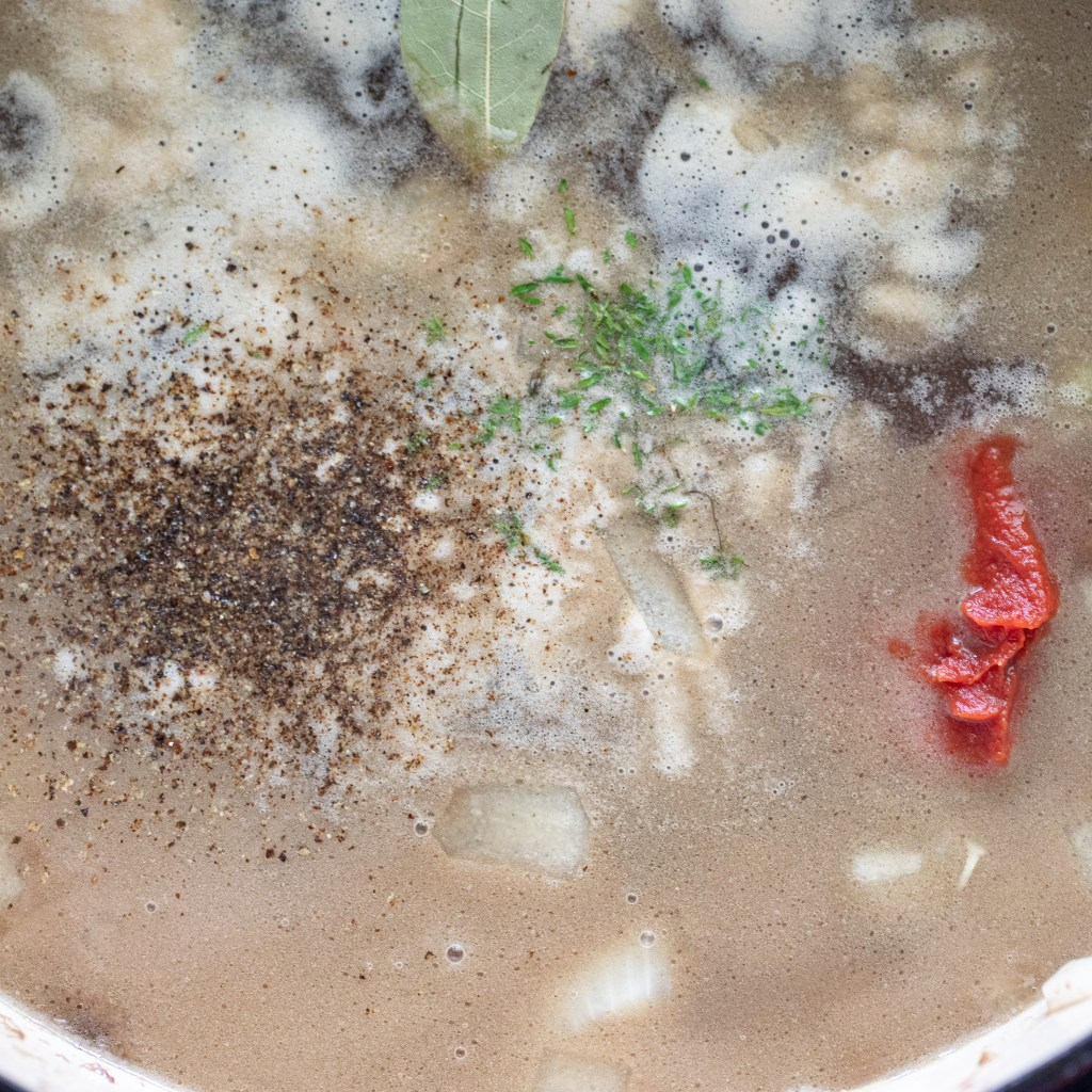 beef stock added to enameled dutch oven with beef and veggies