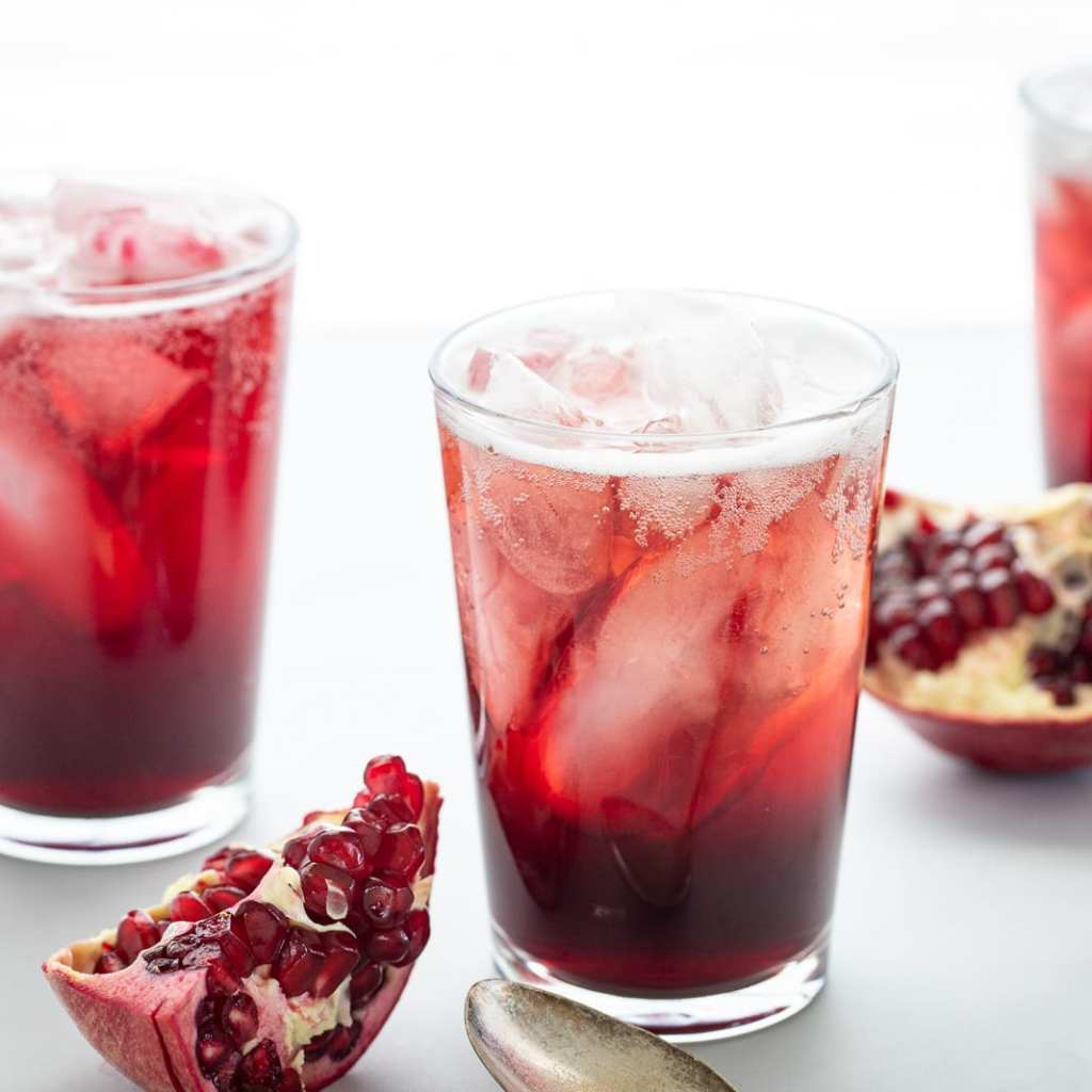 Simple Vanilla Pomegranate Fizz in clear glass cups with pomegranates