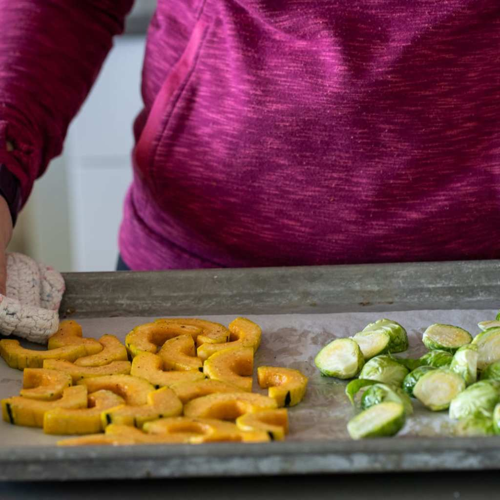 woman with delicata squash and brussel sprouts on a parchment-lined baking sheet.