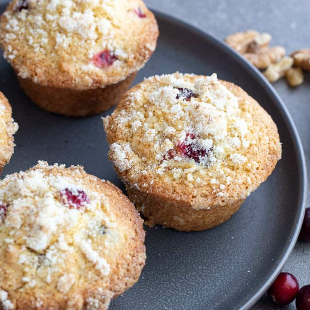 Cranberry Orange muffins on a gray plate with cranberries and walnuts in the background