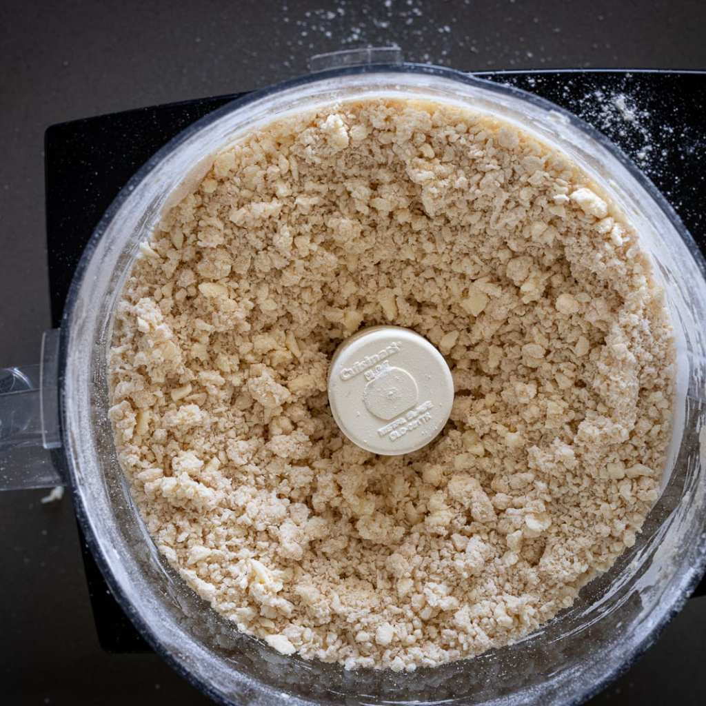 partial wheat pie dough being mixed in Cuisinart food processor