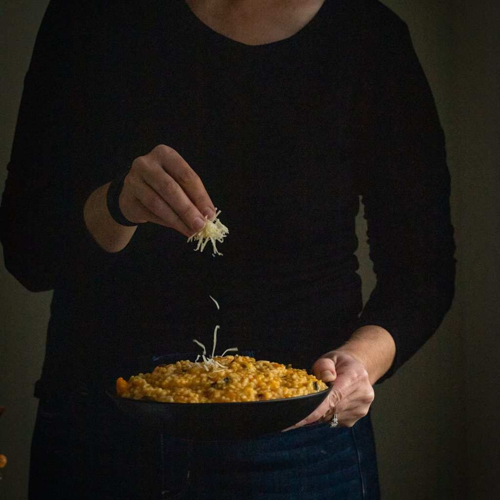 woman sprinkling parmesan cheese over butternut risotto with mushrooms and kale