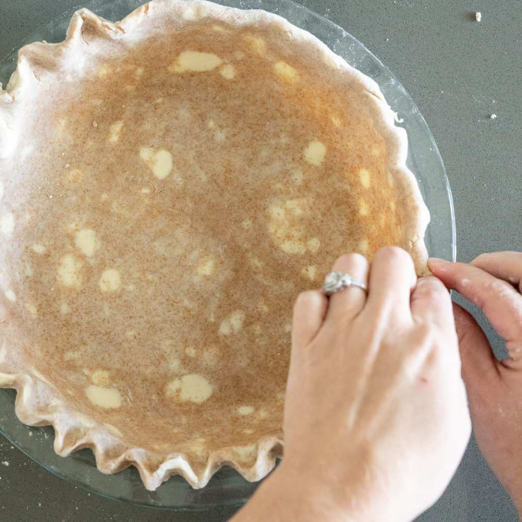 woman crimping pie dough in pie plate for apple pie