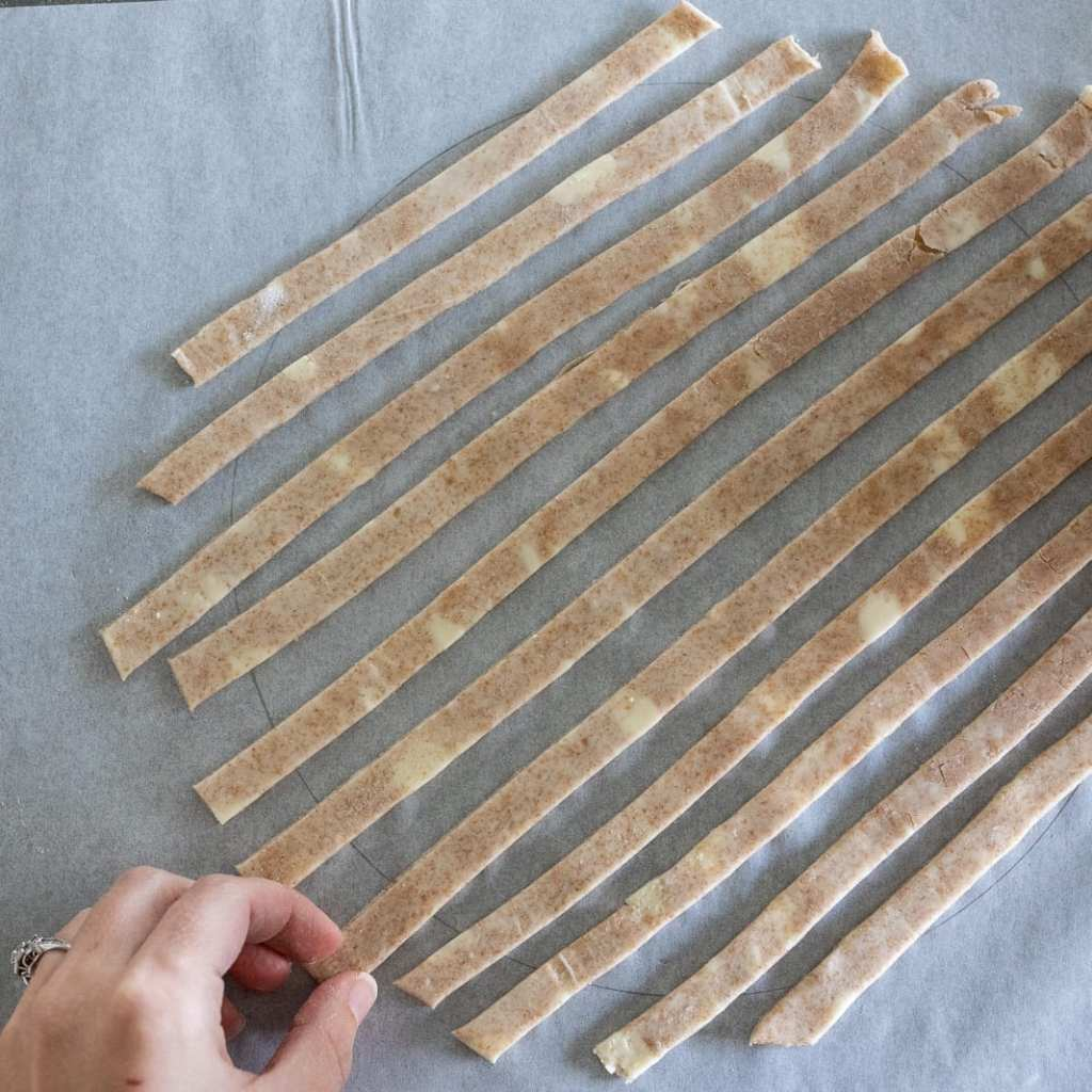 woman placing strips on parchment paper to create lattice work for pie topping