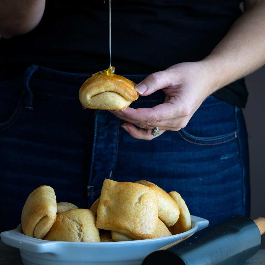 woman pouring honey over a homemade parker house dinner roll