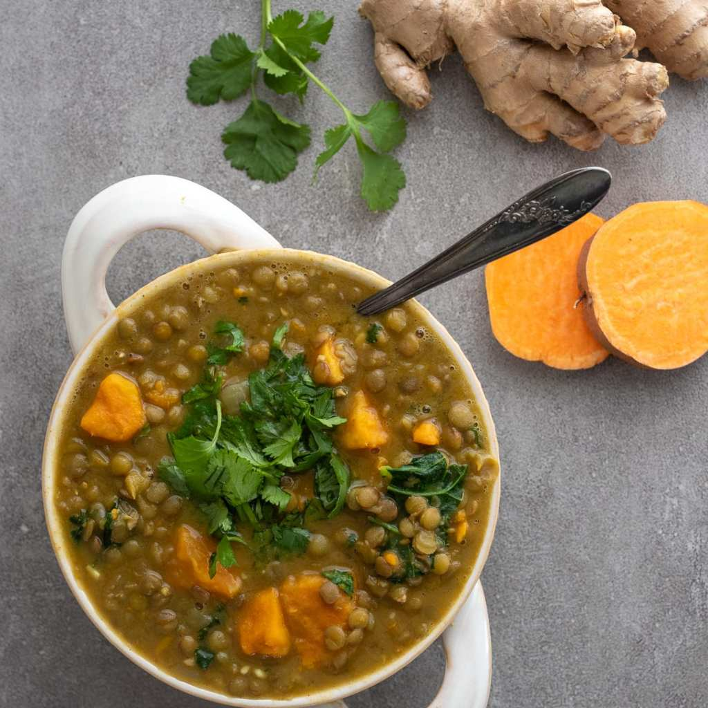 Simple Lentil and Sweet Potato Soup in a white crock with ginger and sweet potatoes on the slate surface