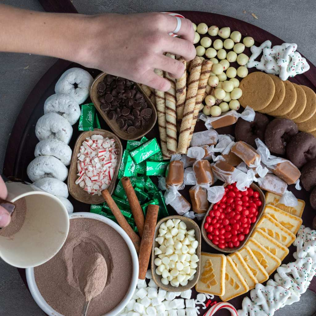 hands reaching for foods on a hot cocoa charcuterie board