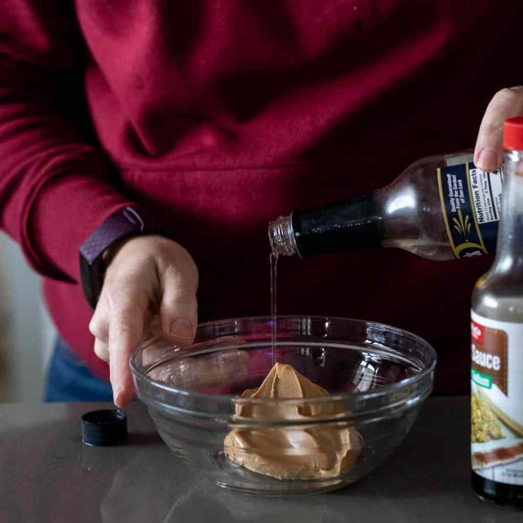 woman pouring rice vinegar into glass bowl with peanut butter for Asian peanut butter dressing