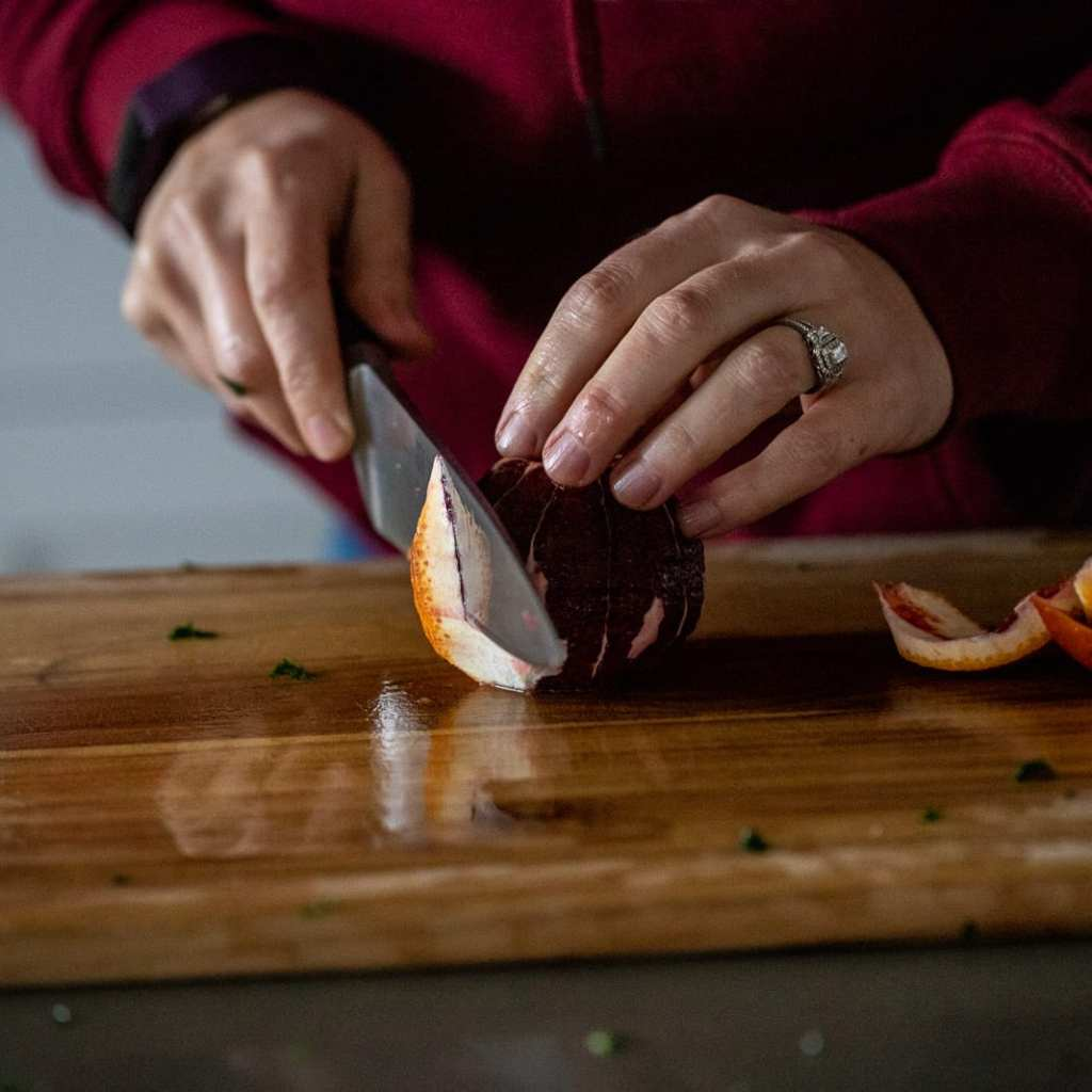 woman cutting blood oranges into slices on a wooden cutting board