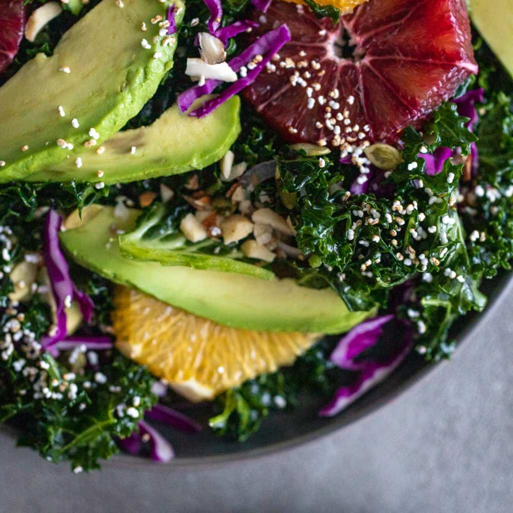 simple healthy salad with kale, blood oranges, avocado, popped amaranth, pepitas, chopped almonds
