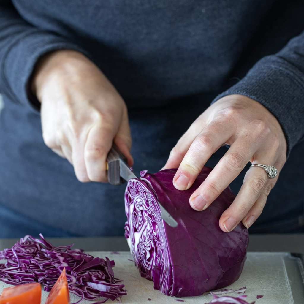 a woman slicing red cabbage on a plastic cutting board