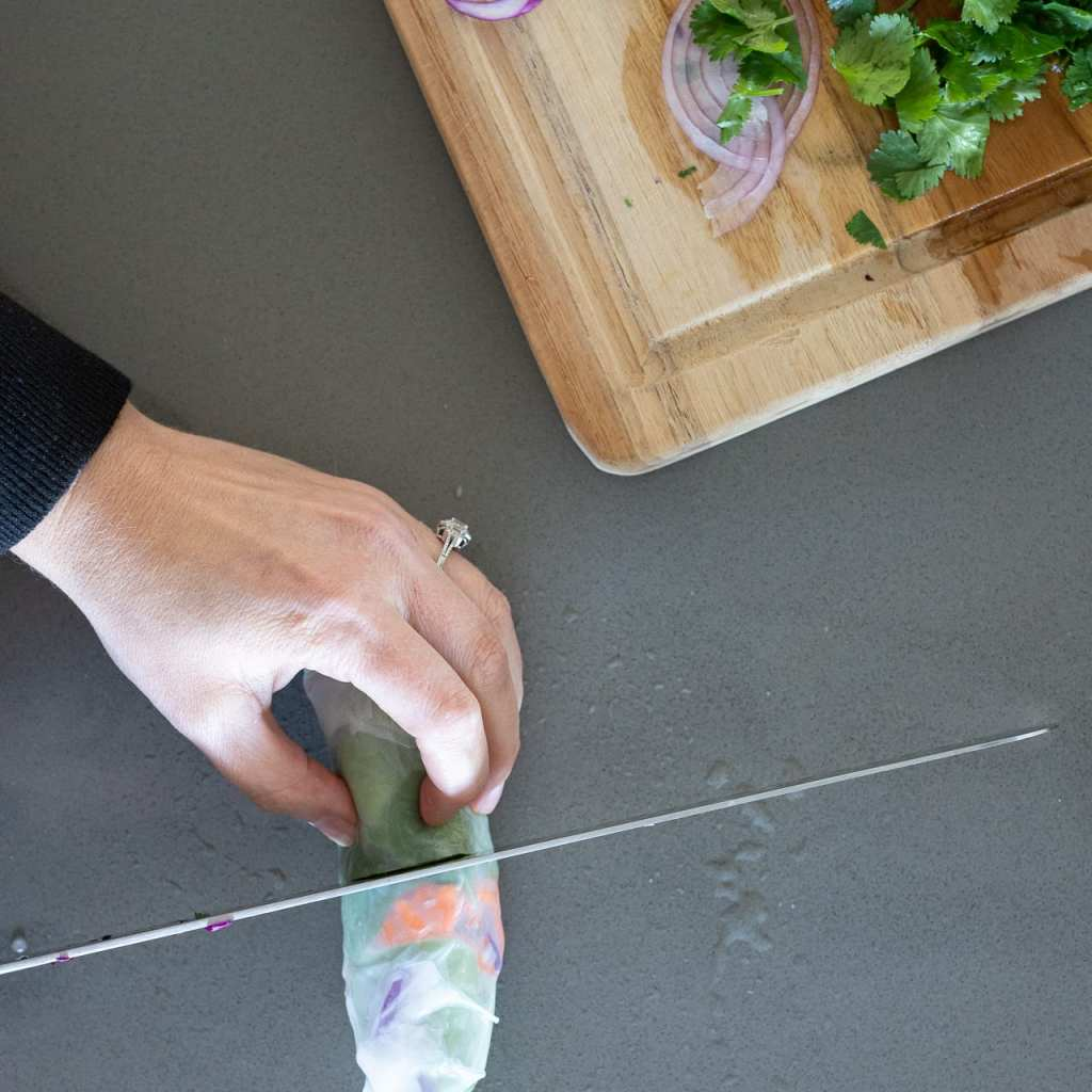woman cutting a spring roll in half with a long sharp knife
