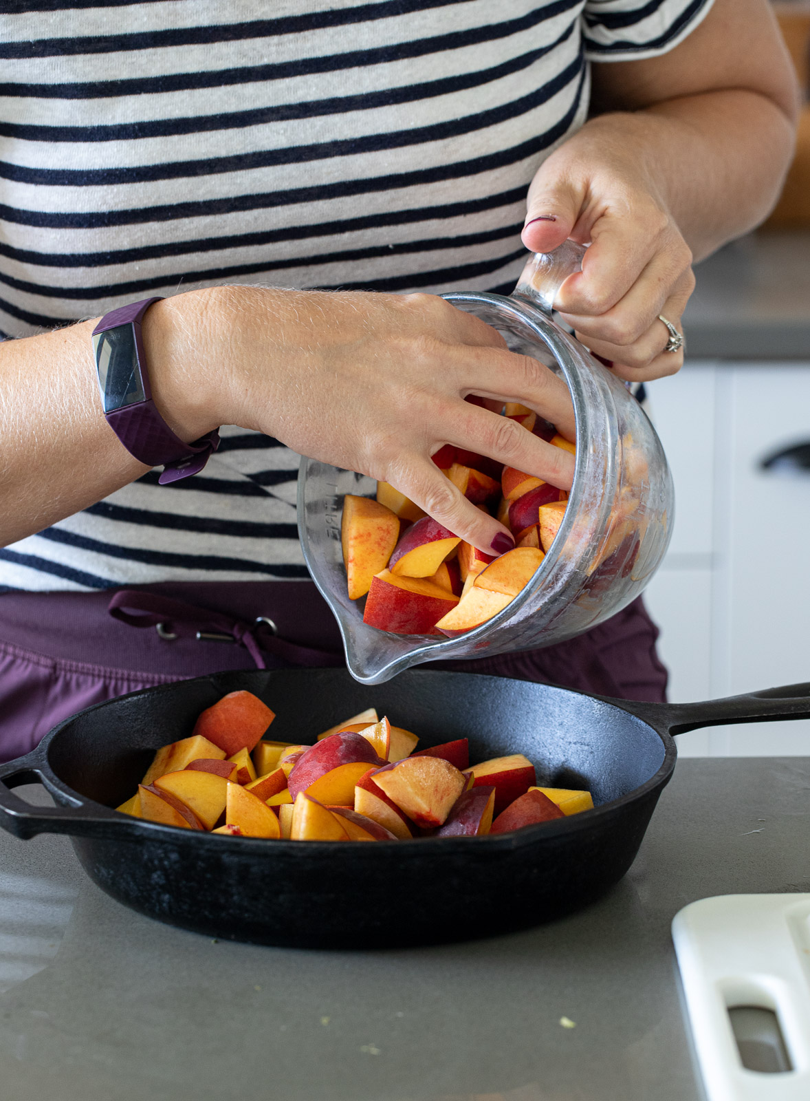 Woman adding peaches to a cast iron skillet.