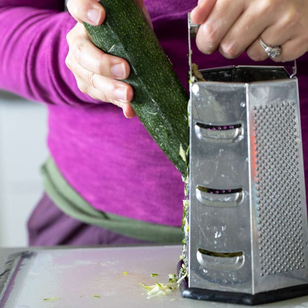 Woman grating zucchini on a box grater.