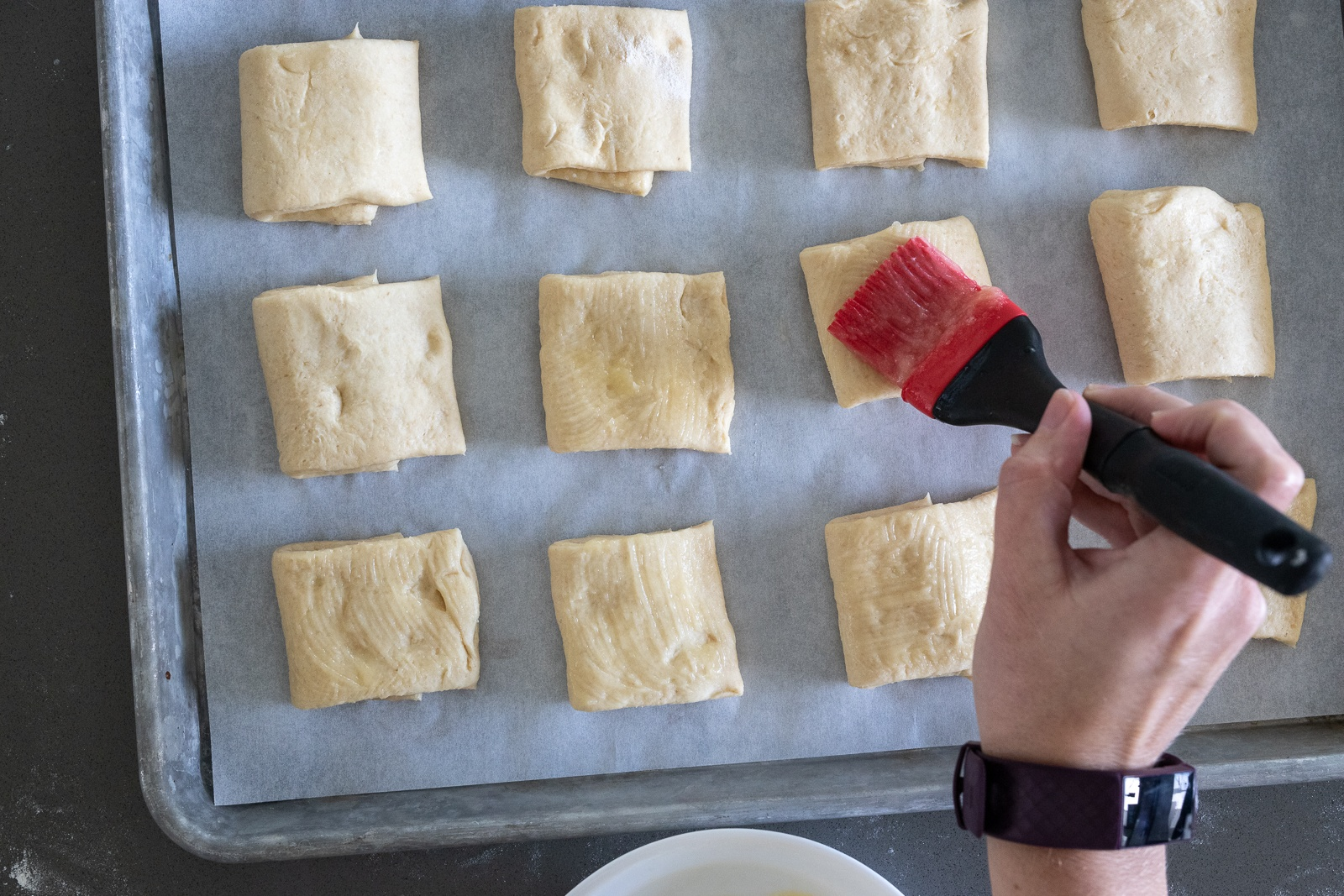 Woman brushing the top of rolls with melted butter.