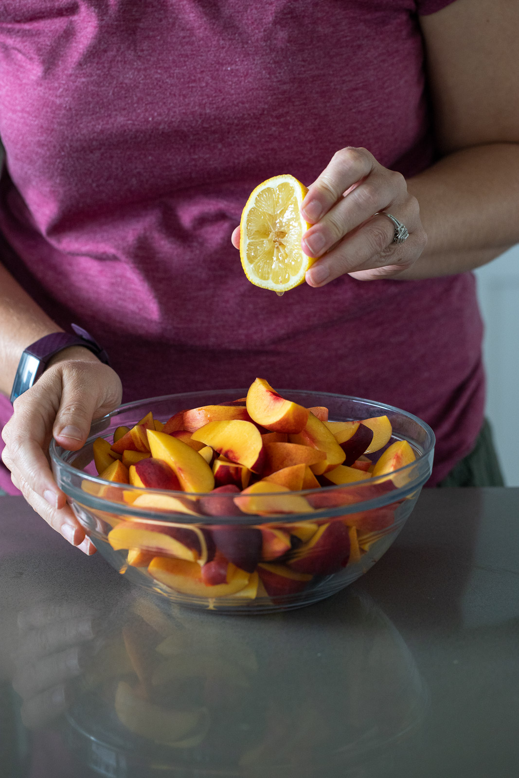 woman squeezing lemon juice onto nectarines in a glass bowl.