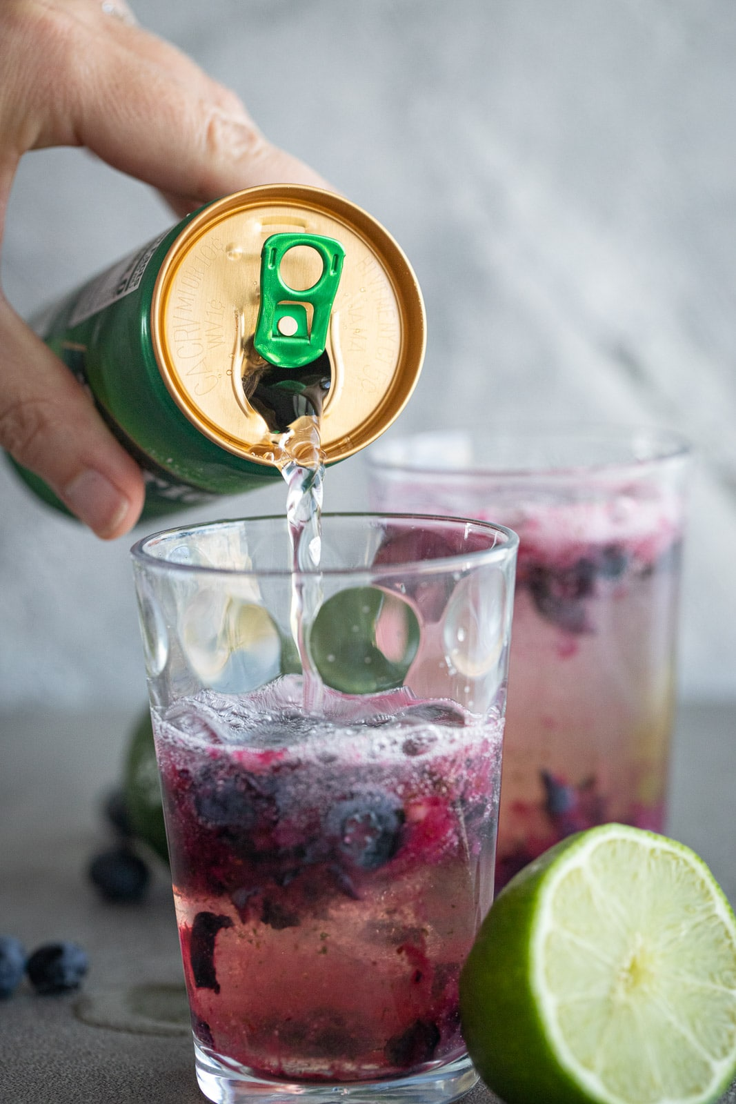 woman pouring perrier sparking water into a mocktail.