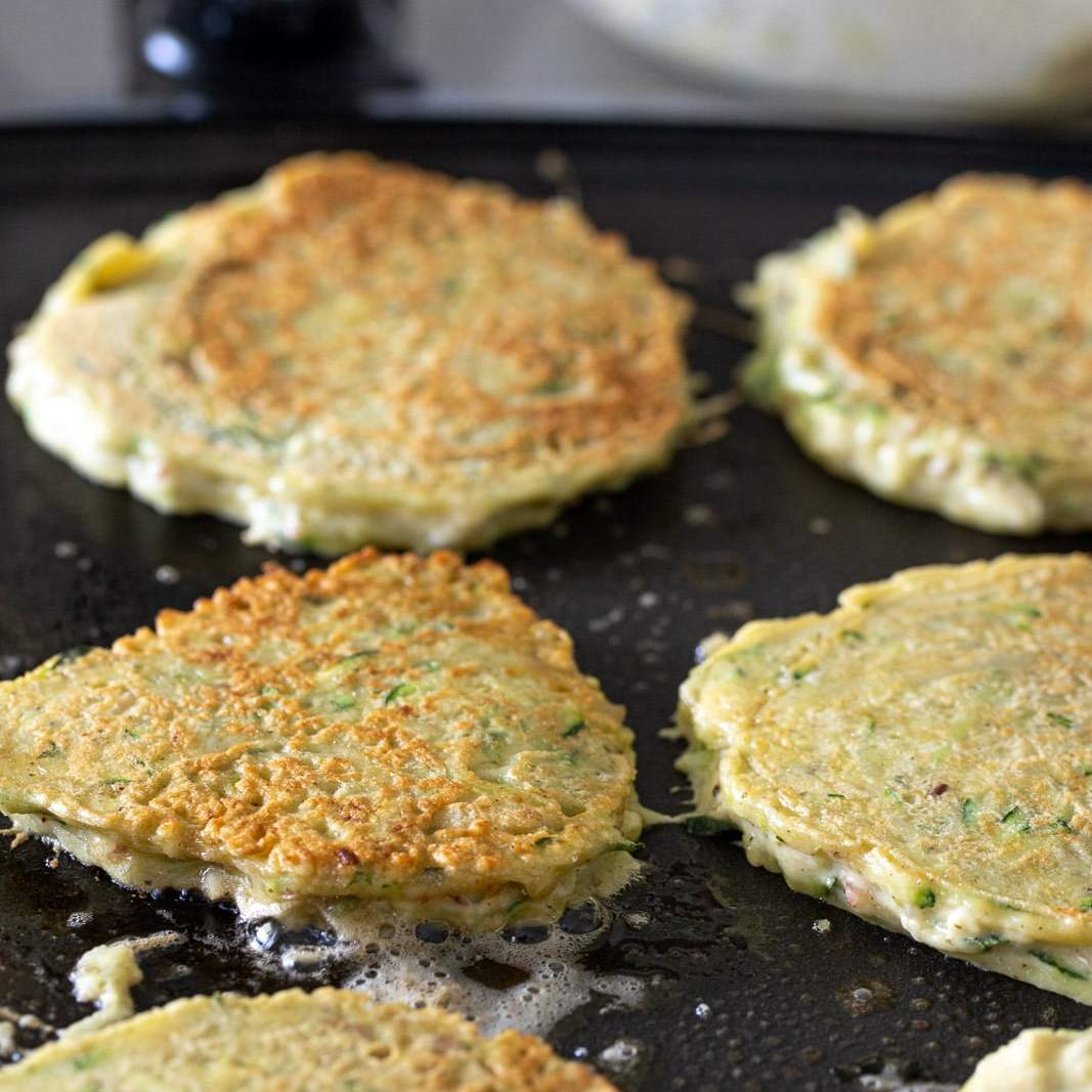 healthy zucchini potato fritters cooking on a greased griddle.