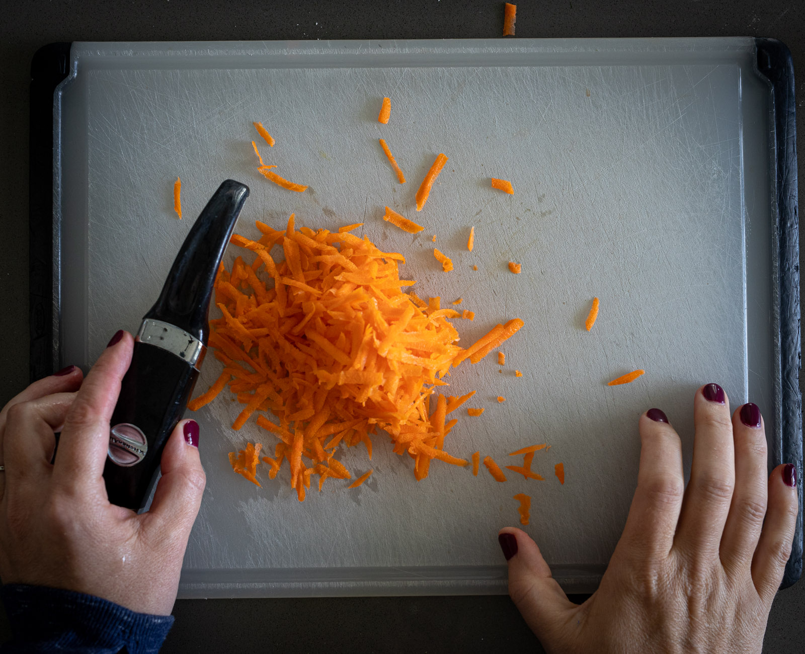 Grated carrots on a plastic cutting board.