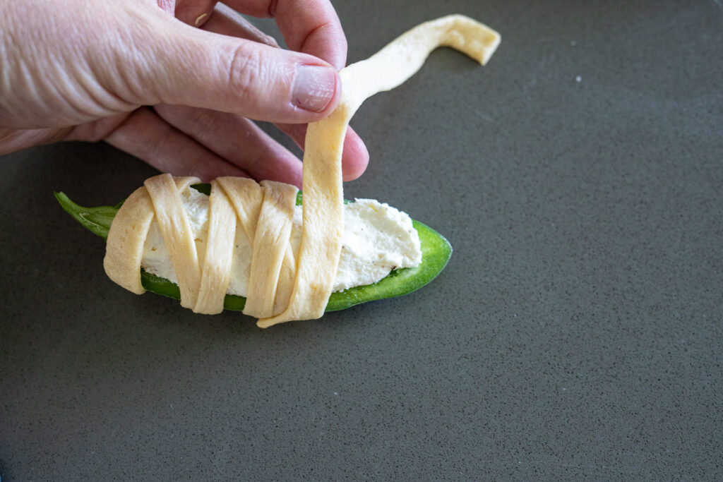 Woman wrapping jalapeno poppers with strips of pillsbury crescent dough.