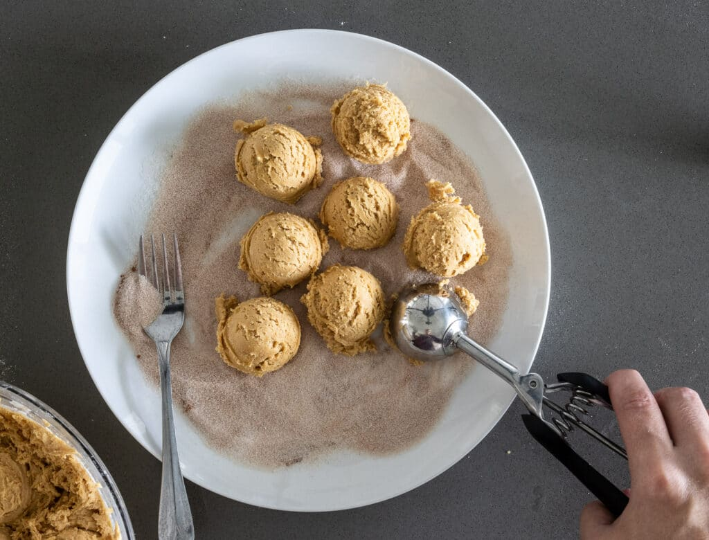 Woman scooping pumpkin snickerdoodle batter onto a plate with cinnamon sugar.