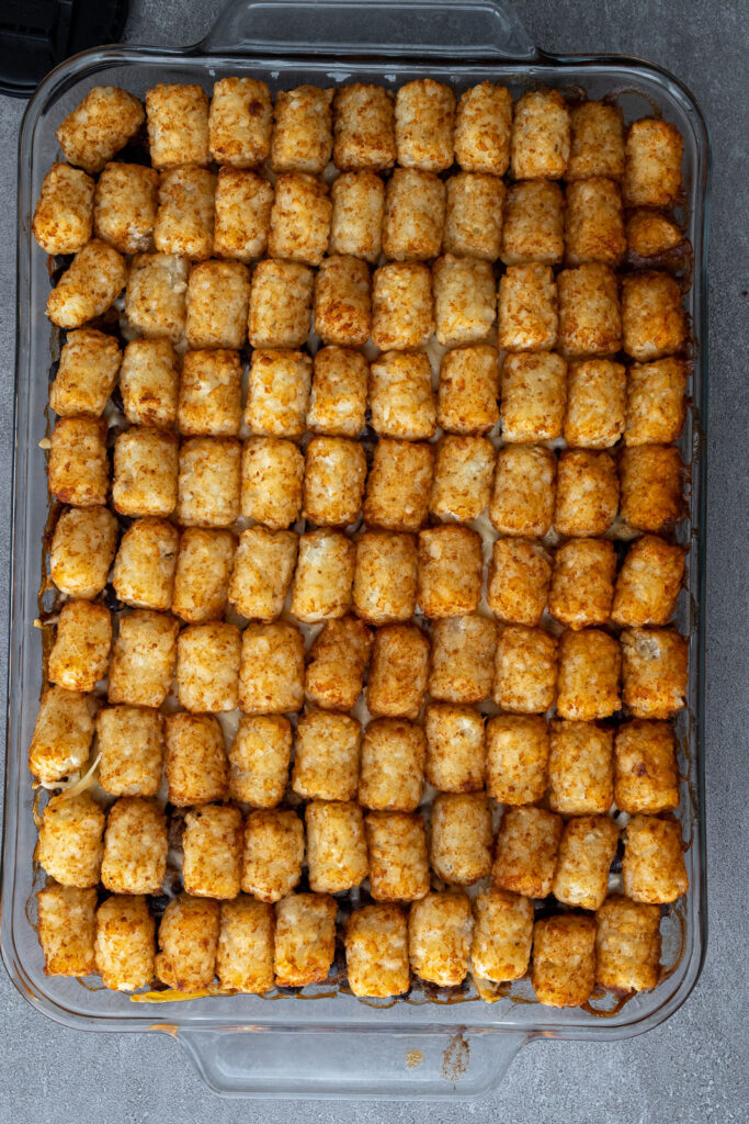 Tater tots lining the top of a casserole.
