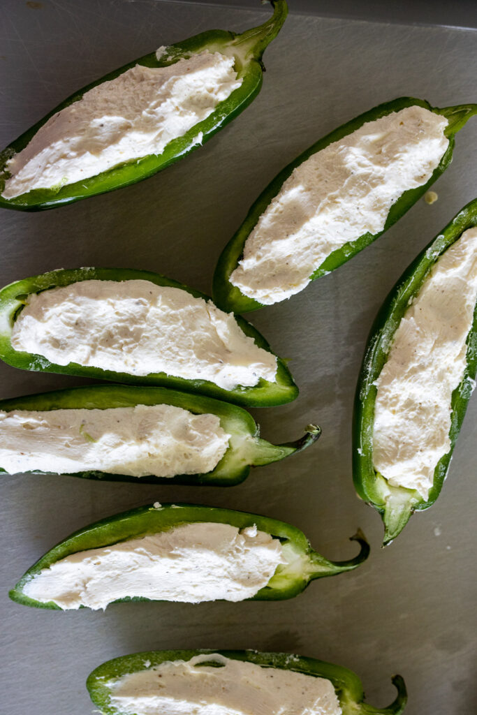 Jalapeno poppers on a white cutting board.