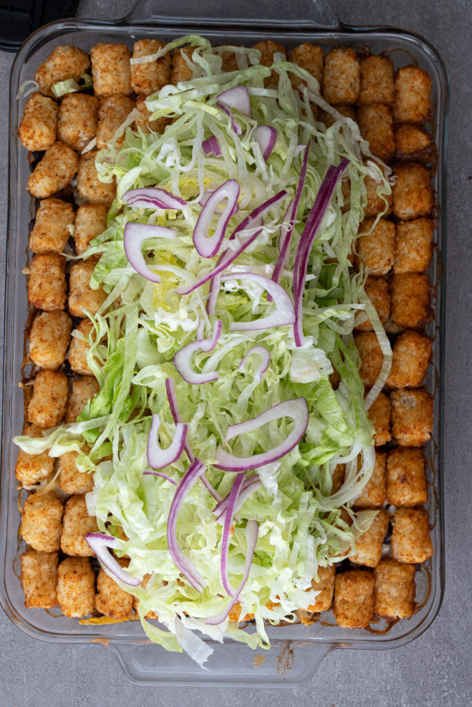 Chopped lettuce and red onions on top of a casserole.