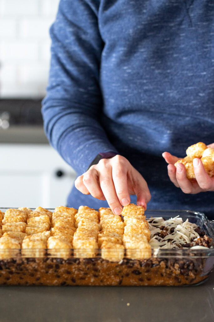 Woman placing tater tots on a casserole.