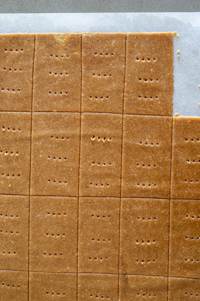 graham cracker dough cut into squares with holes poked in them.