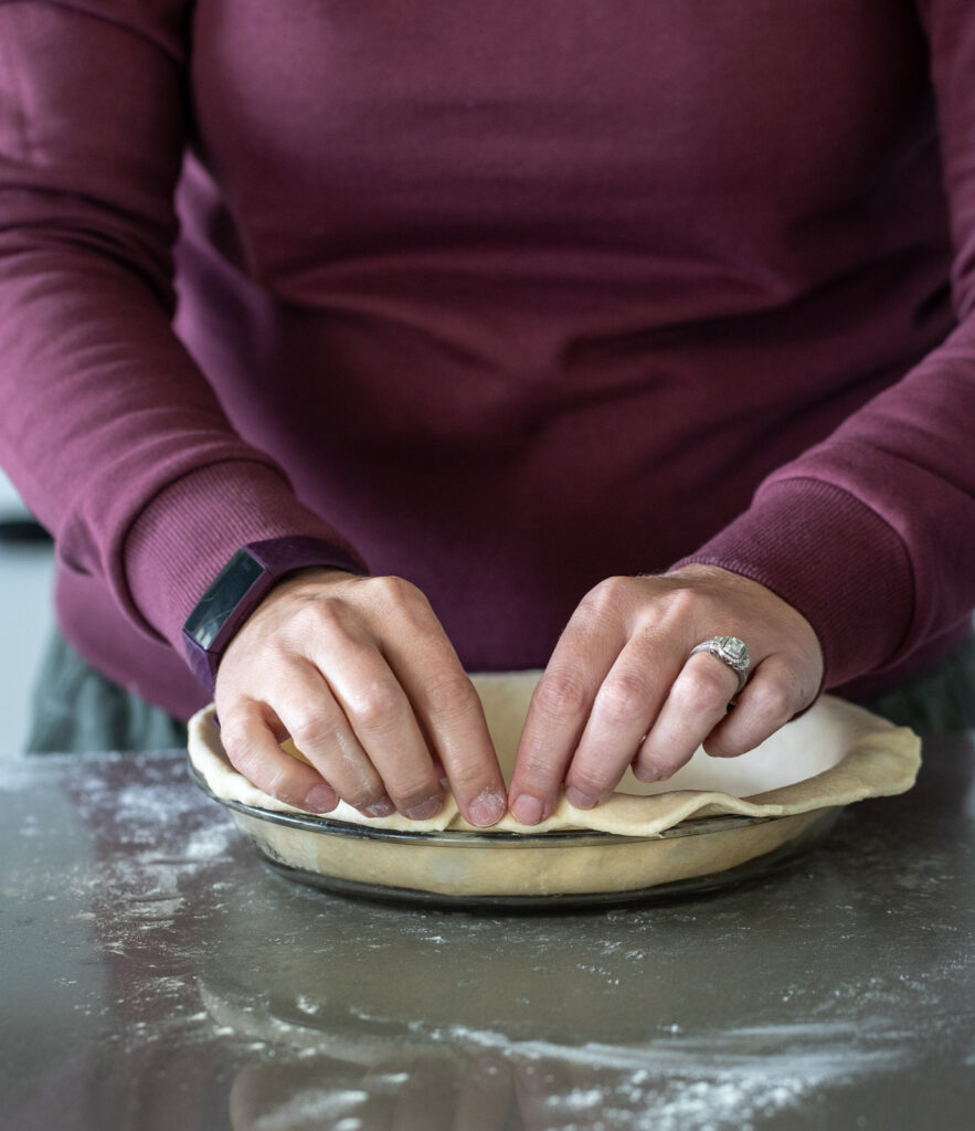 Woman folding over pie crust in a pie pan.