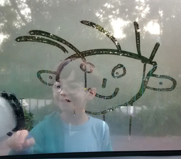 Kid drawing a smiley face in the condensation on a window