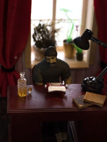 man sitting at typewriter in dollhouse