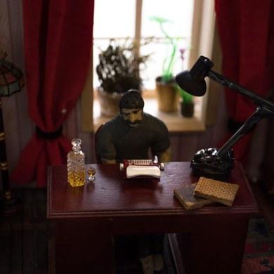 man sitting at typewriter in dollhouse